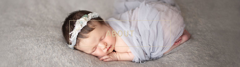 newborn baby girl wrapped in grey, sleeping